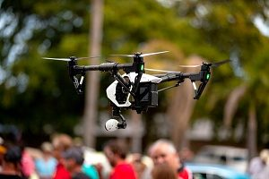 drone that is covered by drone insurance monitoring a crowd of people at an event